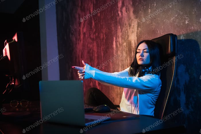 The girl gamer shooting with her fingers to monitors, concept of virtual reality, gaming and esports