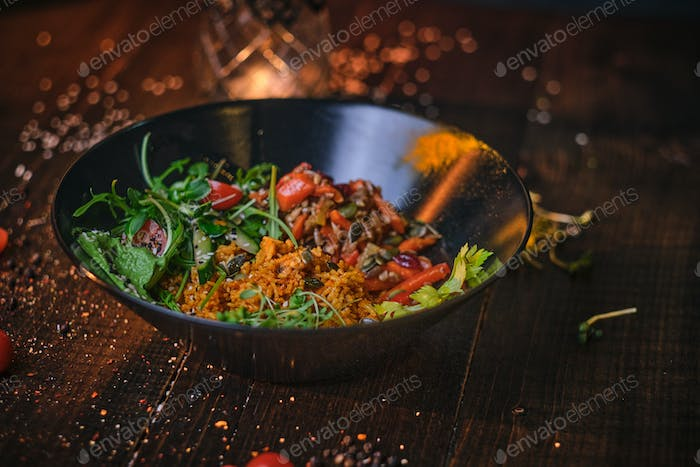 Cooked vegetarian bowl of plov on a wooden table