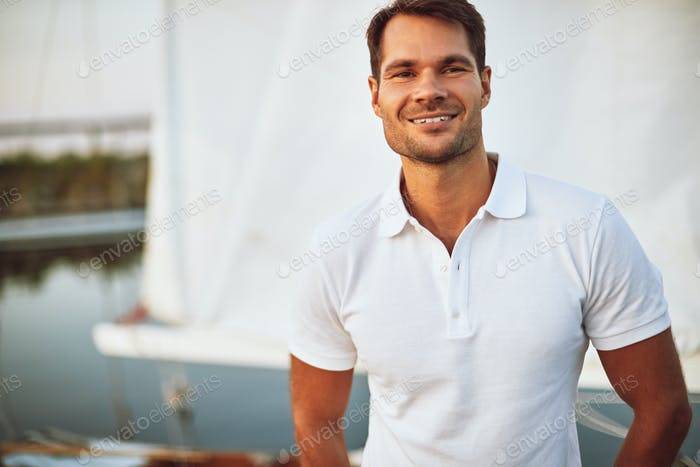 Young man smiling while standing alone on his yacht