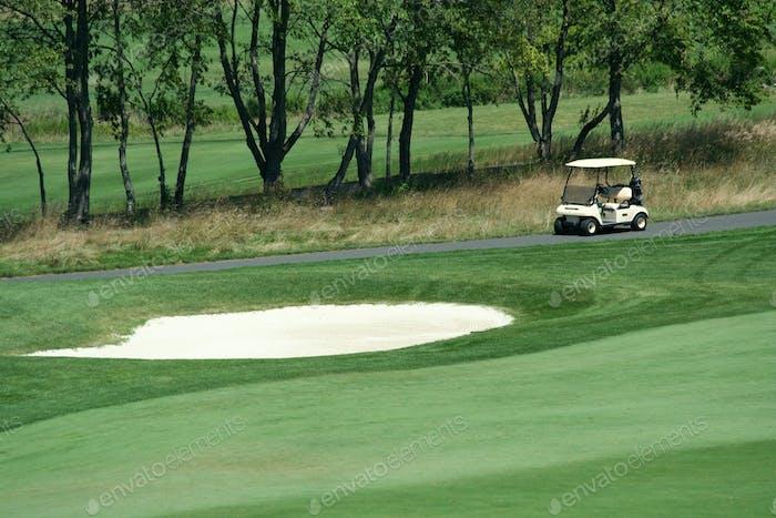 Golf cart parked near a sand trap
