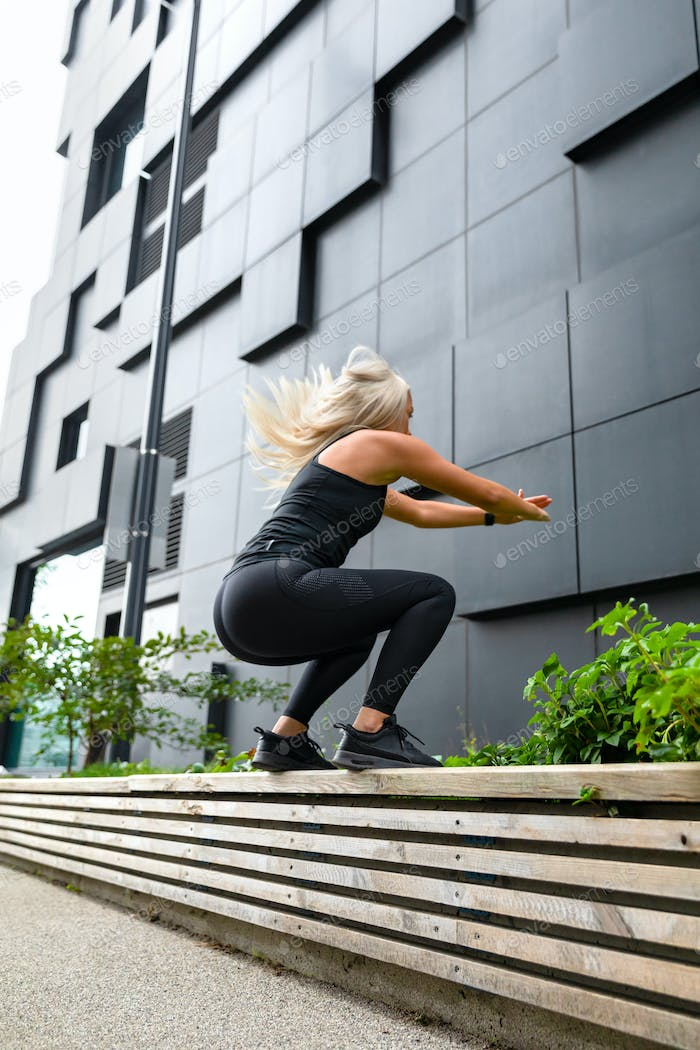 Hardworking fitness woman jumping outdoor in urban enviroment