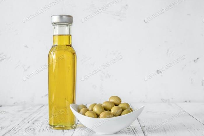 Bottle of olive oil with green olives