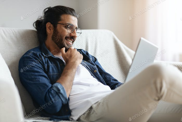 Smiling Western Guy With Digital Tablet Relaxing On Couch At Home