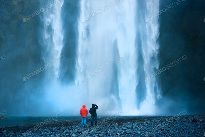 Waterfall wall water full two man near in Iceland