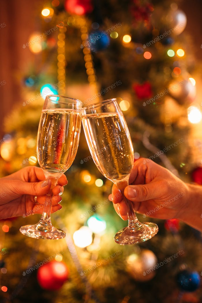 Two hands clink glasses with champagne, christmas