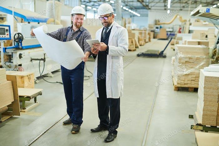 Ingeniero alegre presentando el proyecto al inversor en bata blanca