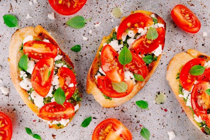 Bruschetta mit Pesto-Sauce, Feta-Käse, Tomaten und Basilikum