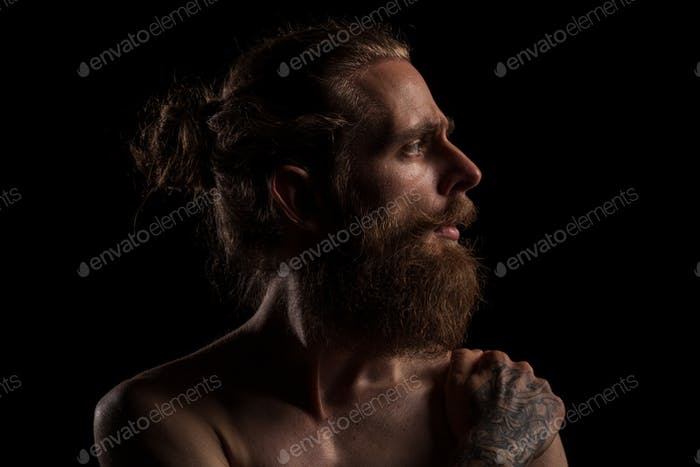 Portrait of cool tattooed bearded hipster guy on black backgroun