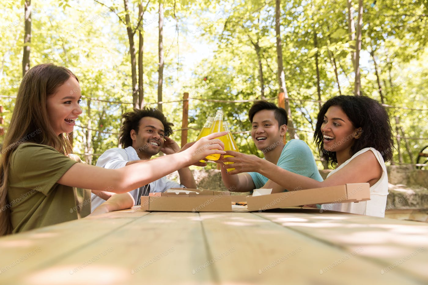 Smiling young multiethnic friends students outdoors drinking juice