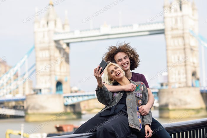 Happy couple taking selfie photograph at the Tower Bridge
