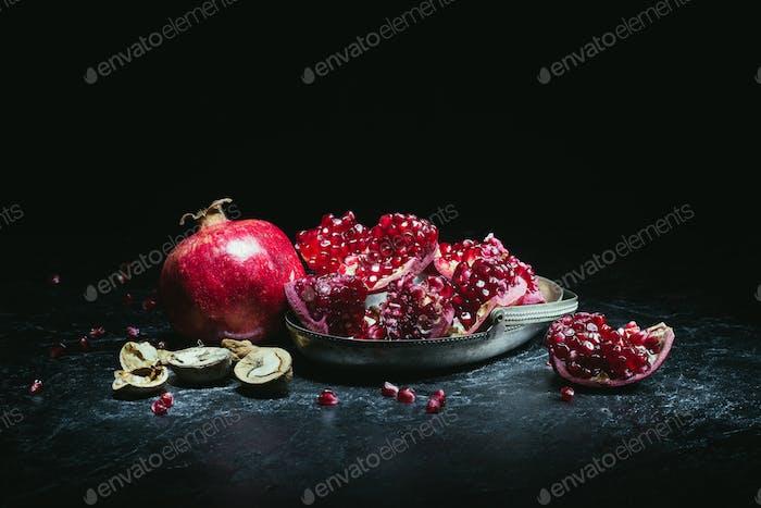 Granatäpfel in Metallschale und Walnüsse auf einem Tisch