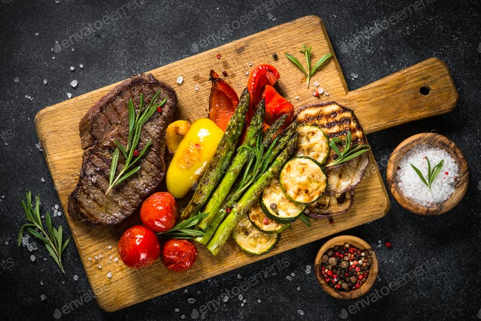 Beef steak grilled with vegetables on black stone table