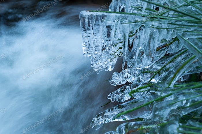icicles on grass by mountain river