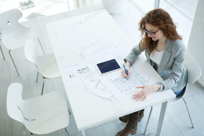 Beautiful female architect working on plan