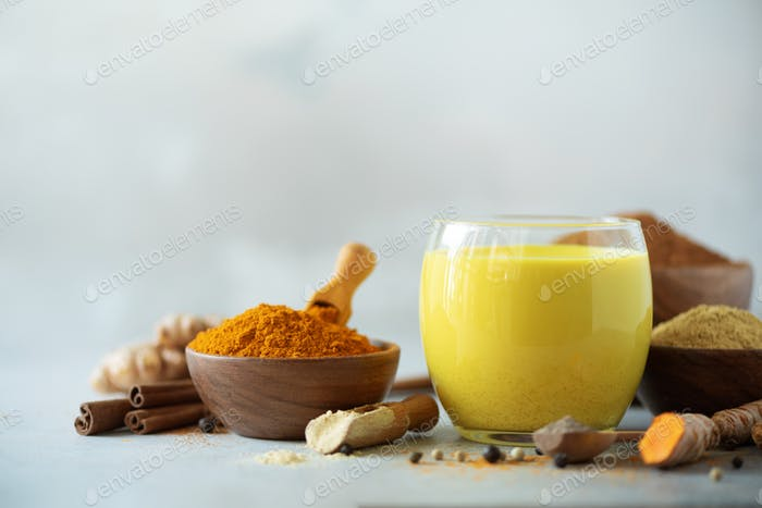 Hot healthy drink. Turmeric latte, golden milk with turmeric root, ginger powder, black pepper over