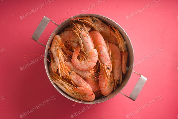 Casserole with shrimp on a bright pink table