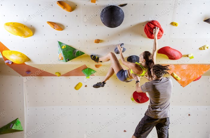 Young woman climbing bouldering problem (route), male instructor
