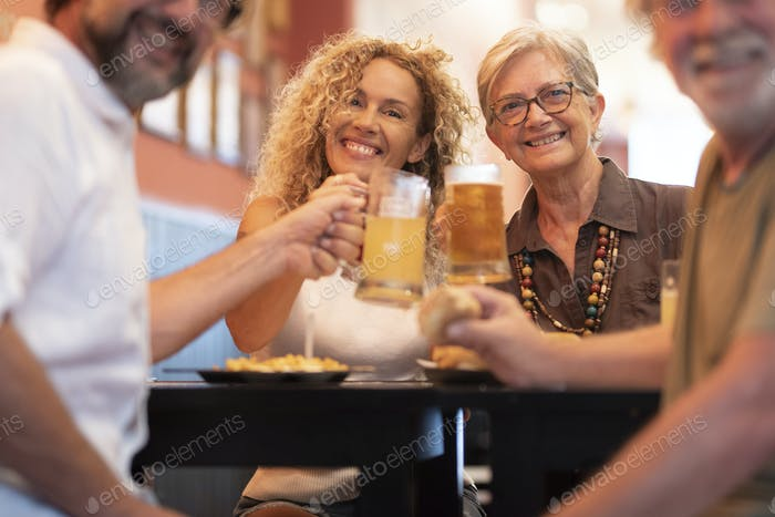 Happy cheerful family having fun and clinking beer glasses together while sitting at table and smile