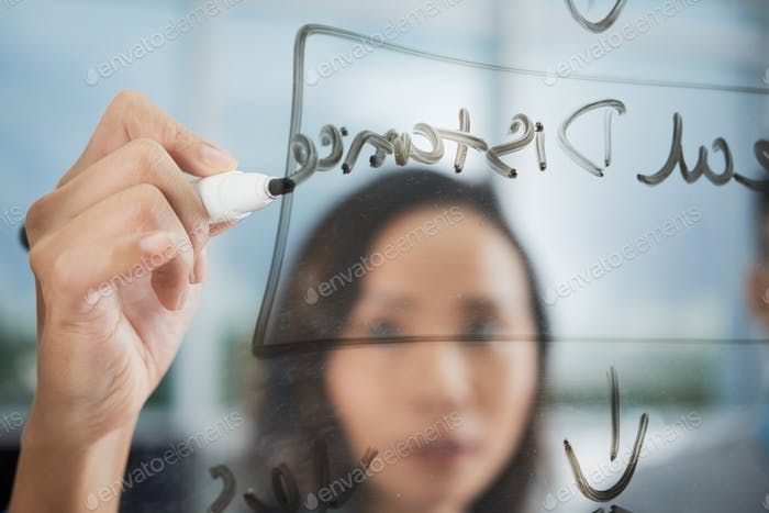 Asian woman writing on transparent board