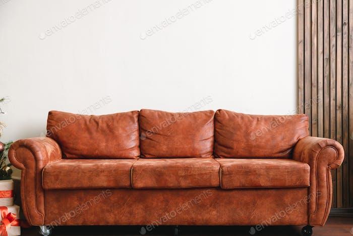 Orangefarbenes Ledersofa mit weißer Wand im Hintergrund