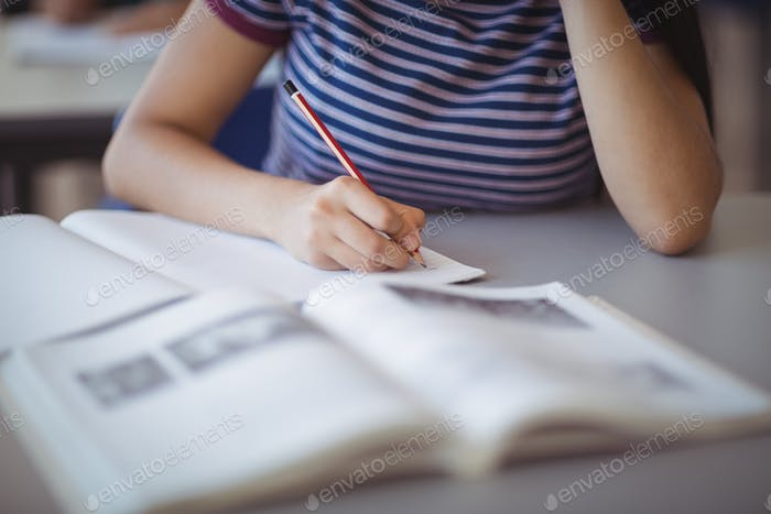 Mid section of schoolgirl studying in classroom