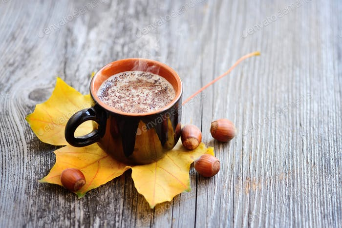Coffee cup on the autumn fall leaves and wooden surface backgrou