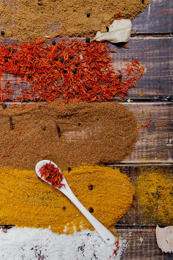 White spoon with saffron near different colorful spices