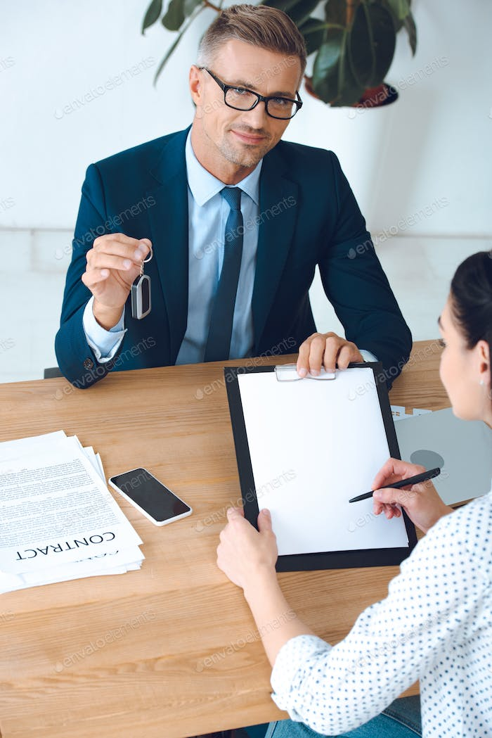 high angle view of smiling insurance agent with car key and client signing papers at workplace in