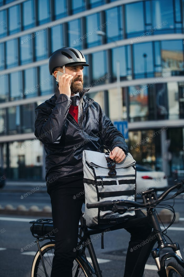 Male courier with bicycle delivering packages in city, making a phone call.