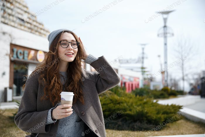 Smiling woman walking and drinking take away coffee outdoors