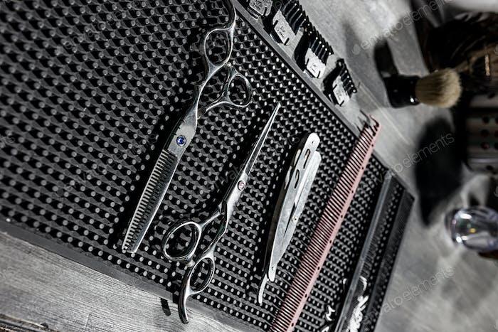 Die Werkzeuge des Friseurs liegen auf einer schwarzen Matte auf dem Desktop