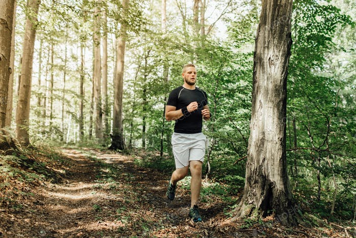 Male runner running along a nature trail through the woods