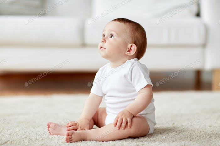 Thumbnail for happy baby boy or girl sitting on floor at home