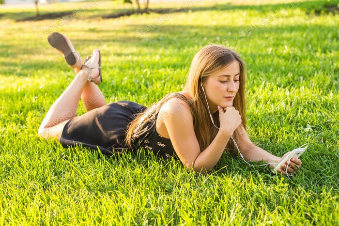 Girl listening to music streaming with headphones in summer on a meadow.
