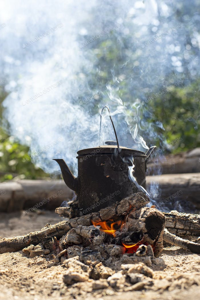 Boiling sooty kettle with hot drink stands on a campfire