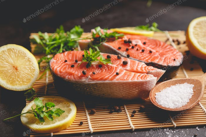 Two salmon steaks with lemon, pepper and salt