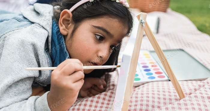 Happy indian little girl having fun painting outdoor at city park - Main focus on girl face