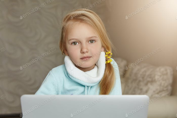 Adorable blonde female school kid with messy ponytail enjoying leisure time at home, sitting in her