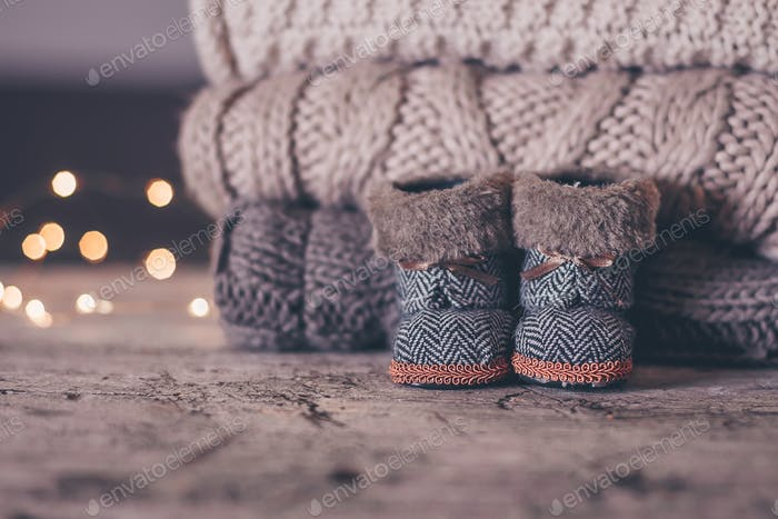 Holiday Christmas Baby Toy Small Boots and Stack Pile of Cozy Knitted Sweaters. Warm Cozy Concept