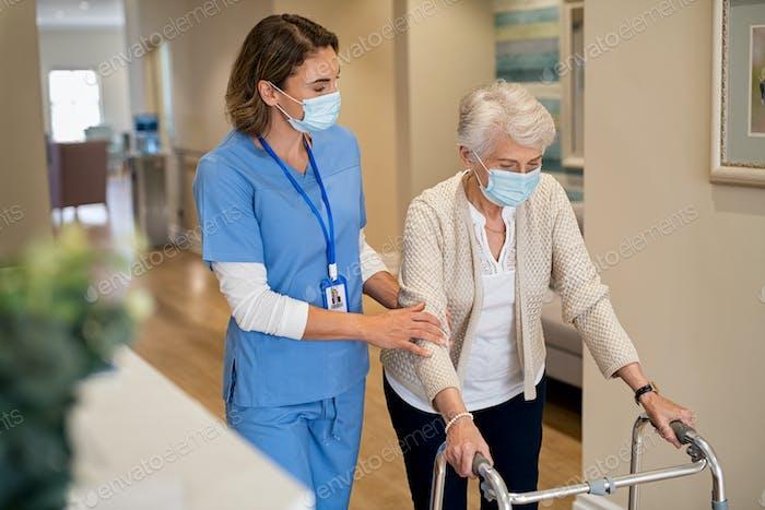 Nurse helping senior woman walk at nursing home