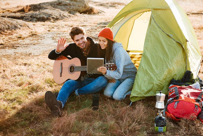 Smiling couple with guitar near the tent