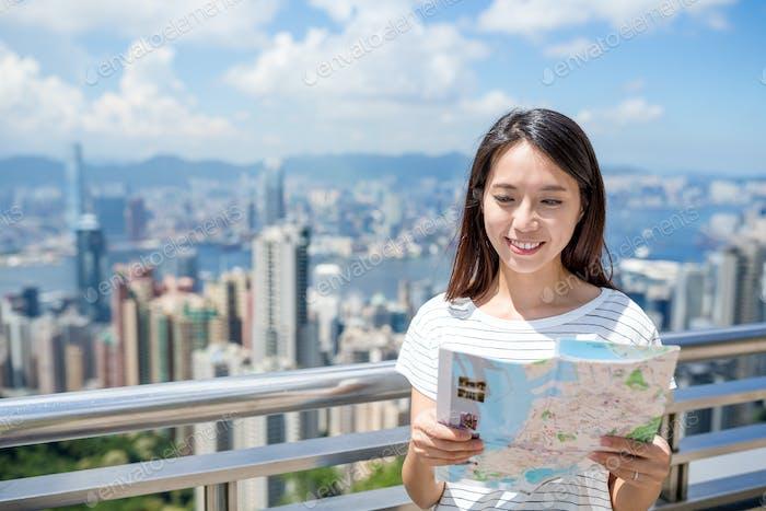 Woman checking on city map in Hong Kong city