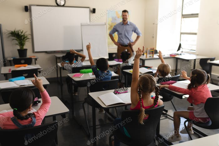 Rear view of school kids raising hand in classroom of elementary school