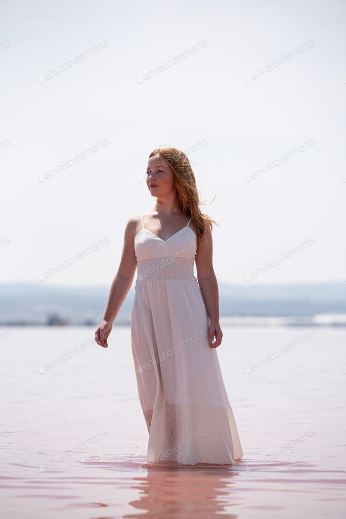 cute teenager woman wearing white dress standing on an amazing pink lake