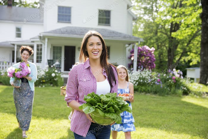 A family gathering. People walking across the lawn carrying flowers and vegetables for a party.
