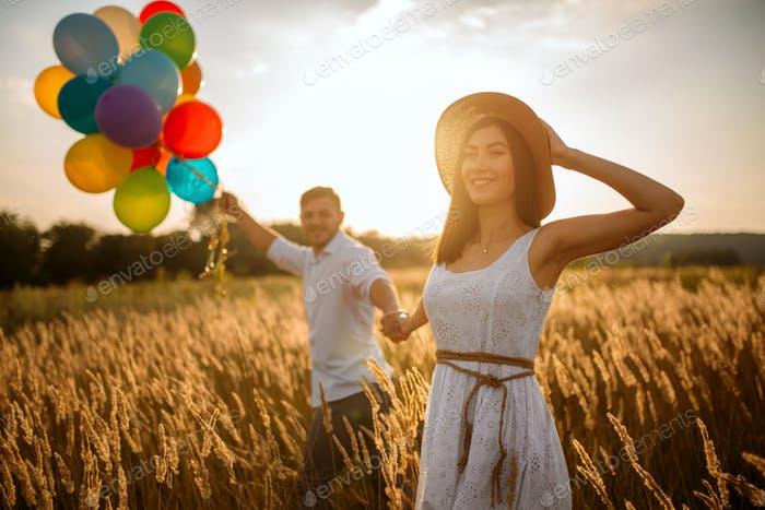 Love couple with balloons, leisure in a rye field