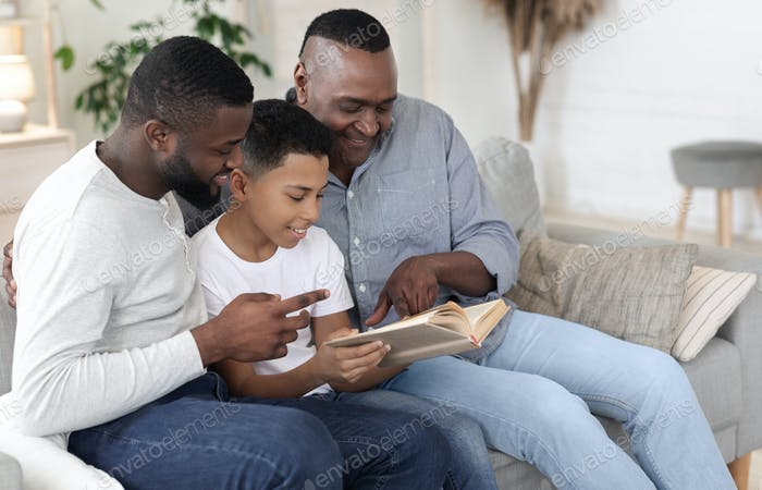 Family Pastime. Happy African Boy Reading Book With Dad And Grandfather Together