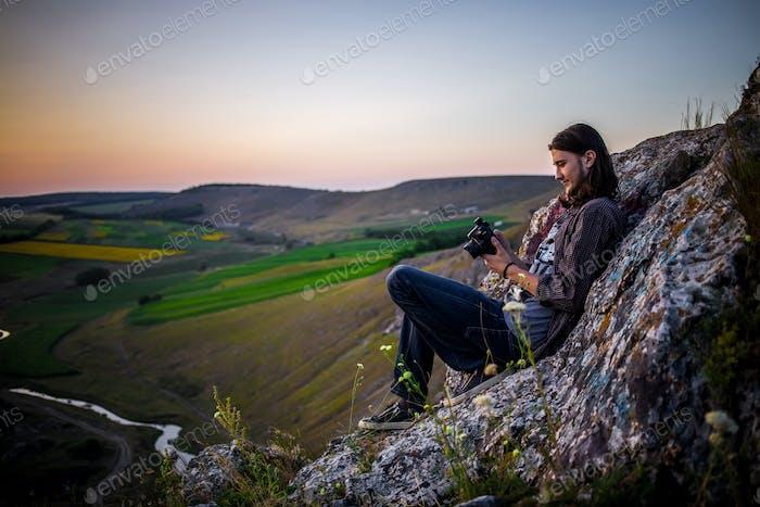 Schönes männliches Modell sitzt auf den Felsen.