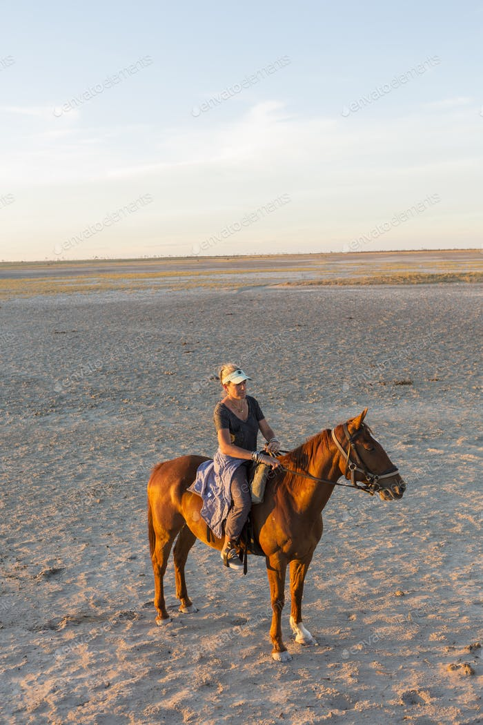 A woman on horseback at sunset in open space.