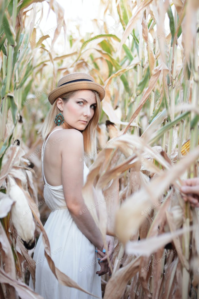 Young caucasian woman in white dress at corn field evening autum